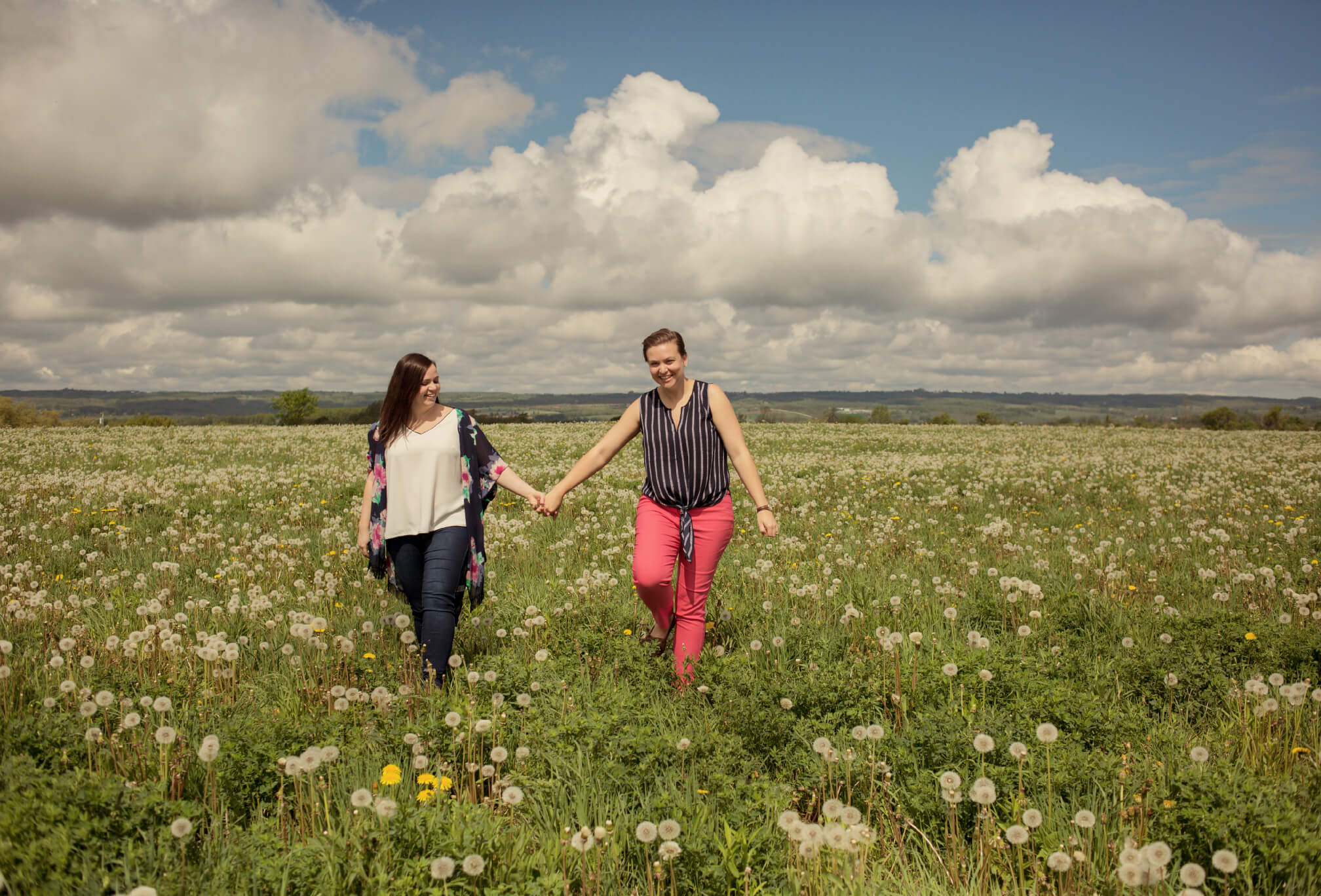 couple walking through flower field