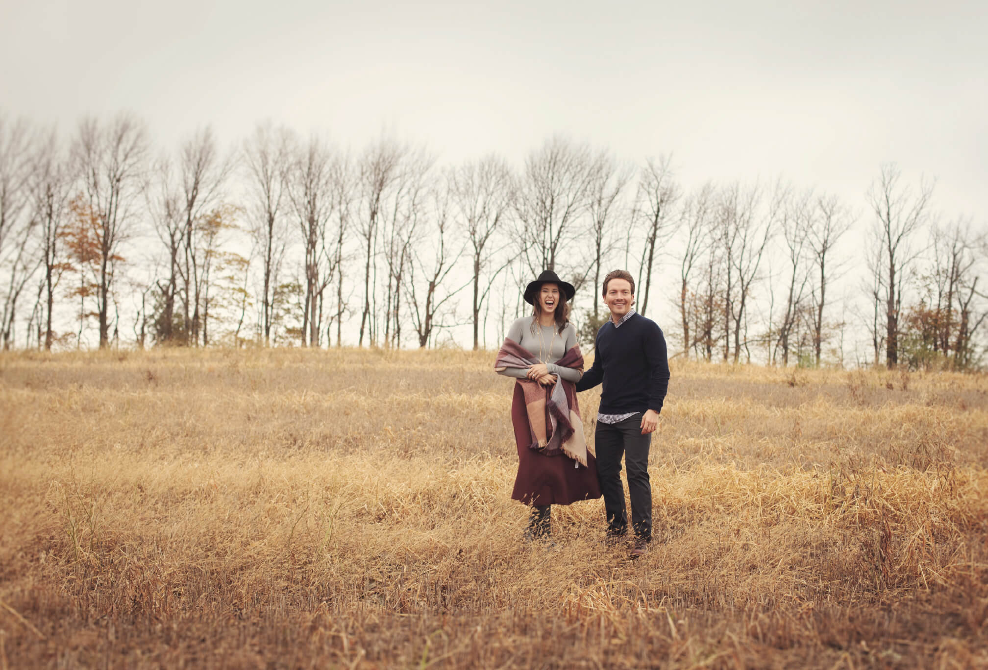 running in a field couple engagement