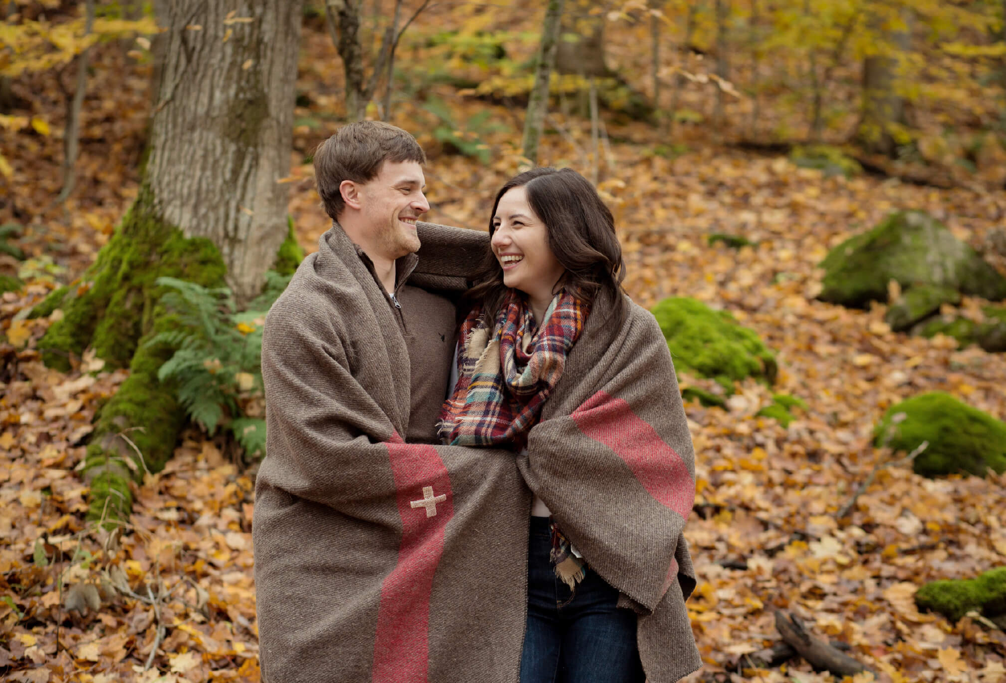 candid couple laughing in forest