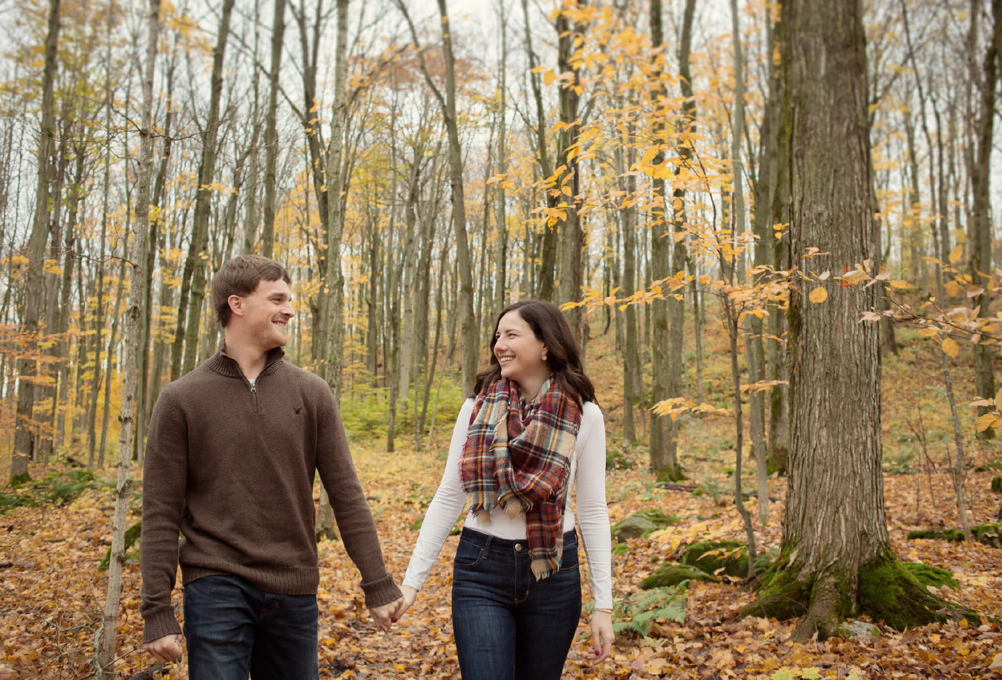 couple walking through forest in fall