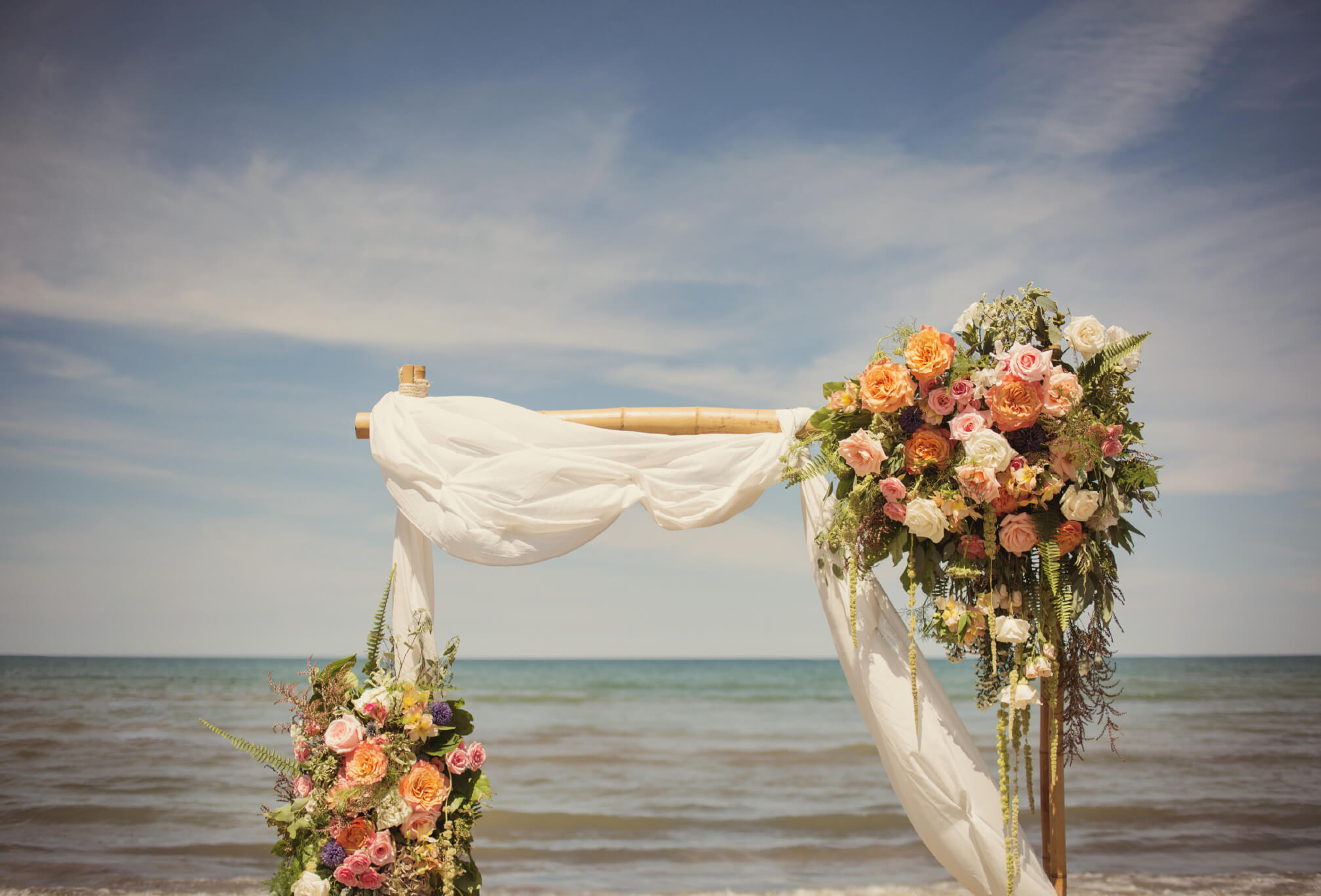 colourful beacfront wedding arbor flowers