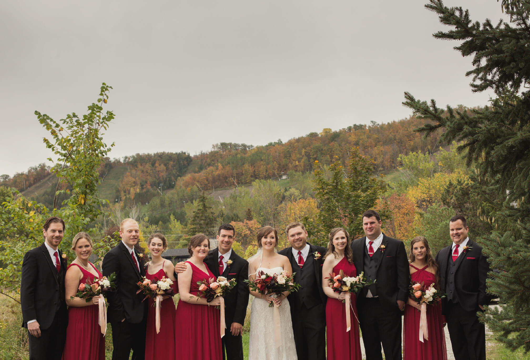 bride and groom and wedding party in fall