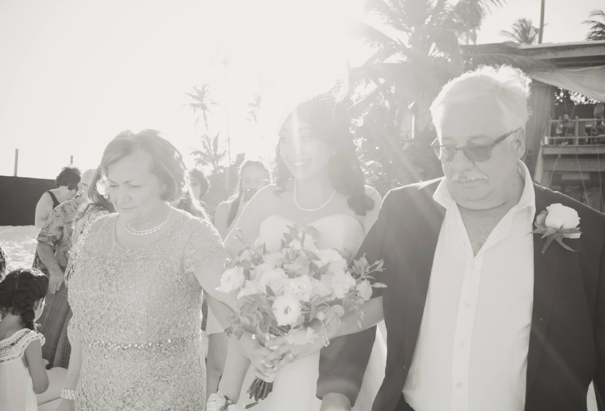 bride and parents walking aisle
