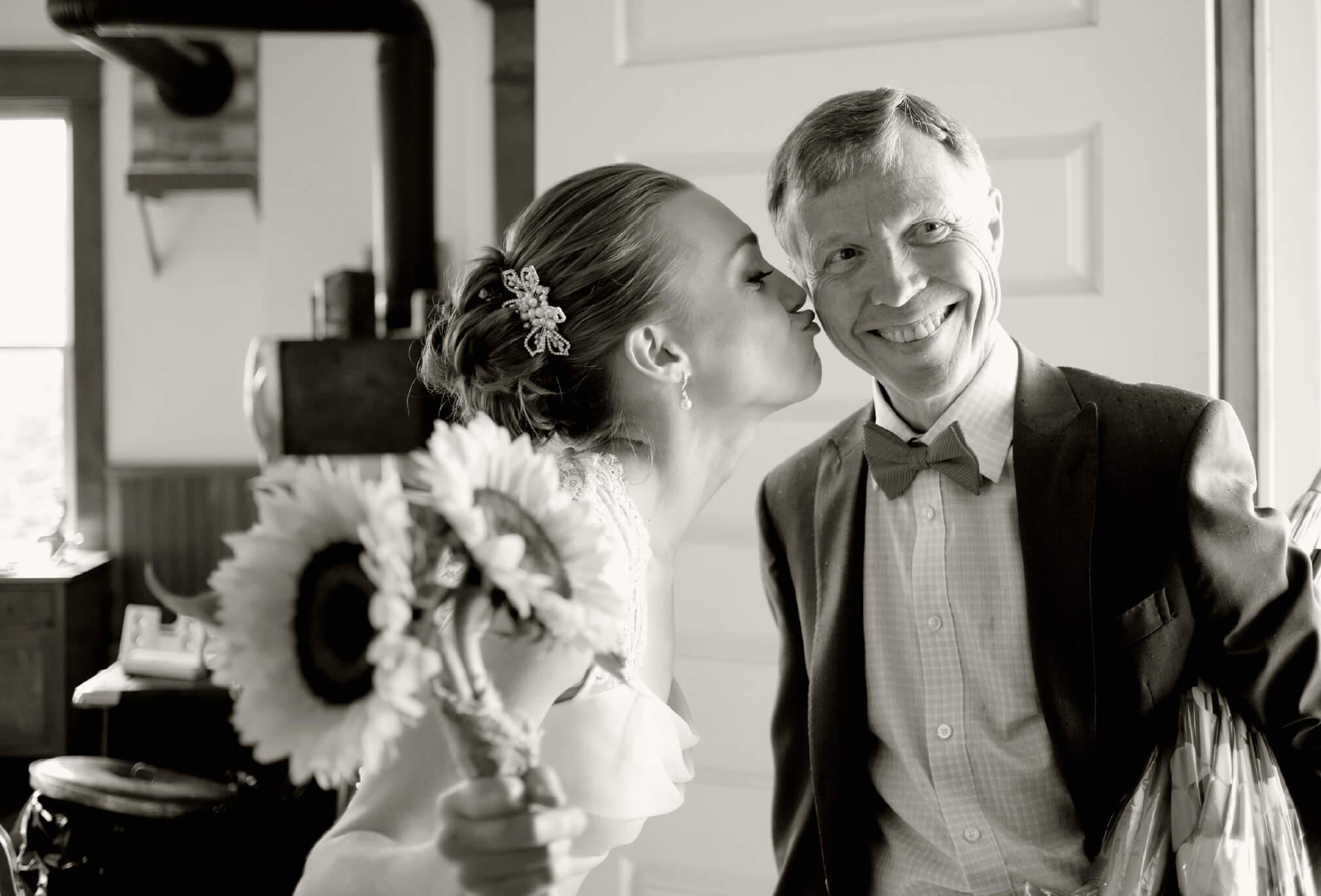 bride kissing dad on cheek