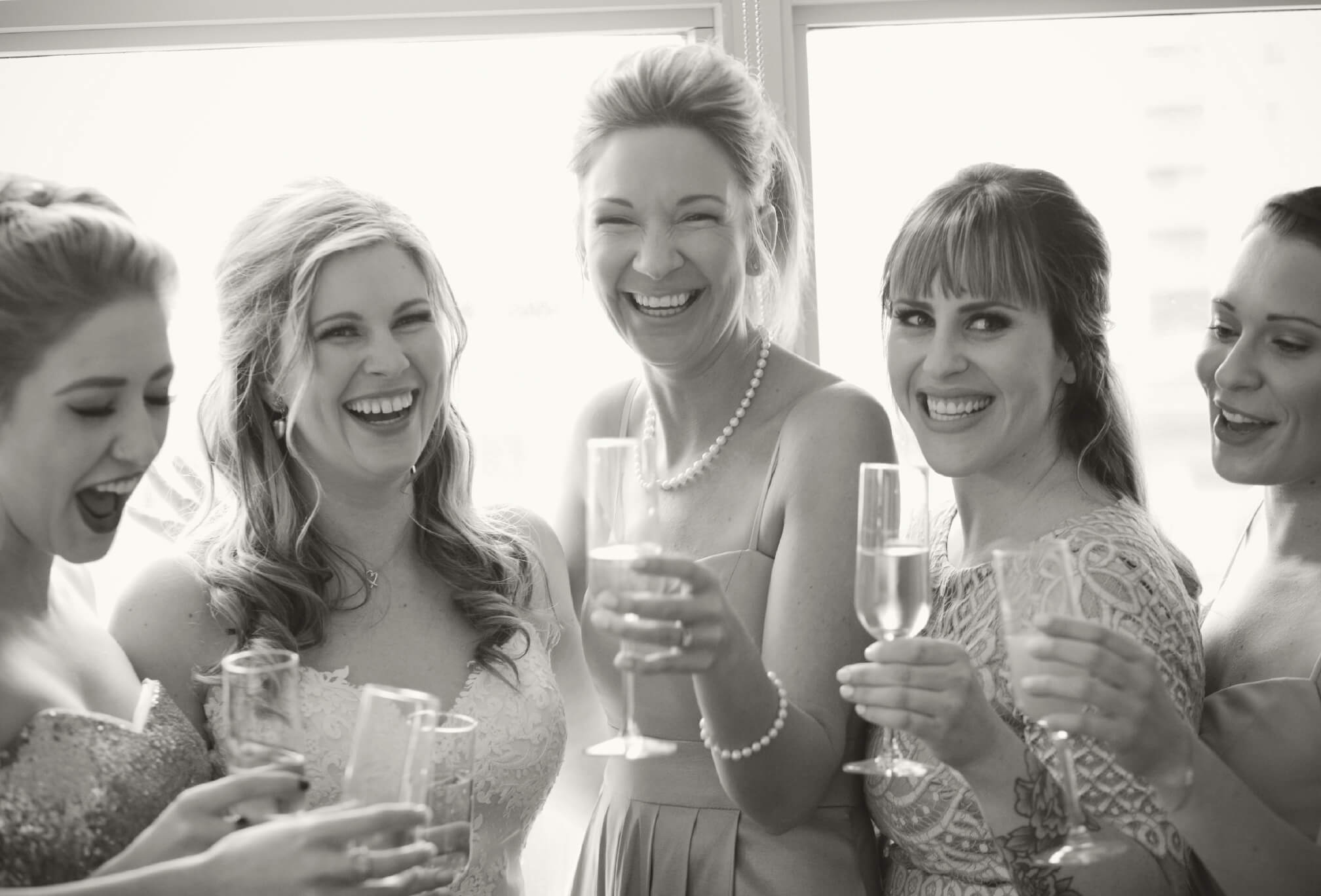 bride and bridesmaids champagne toast laugh