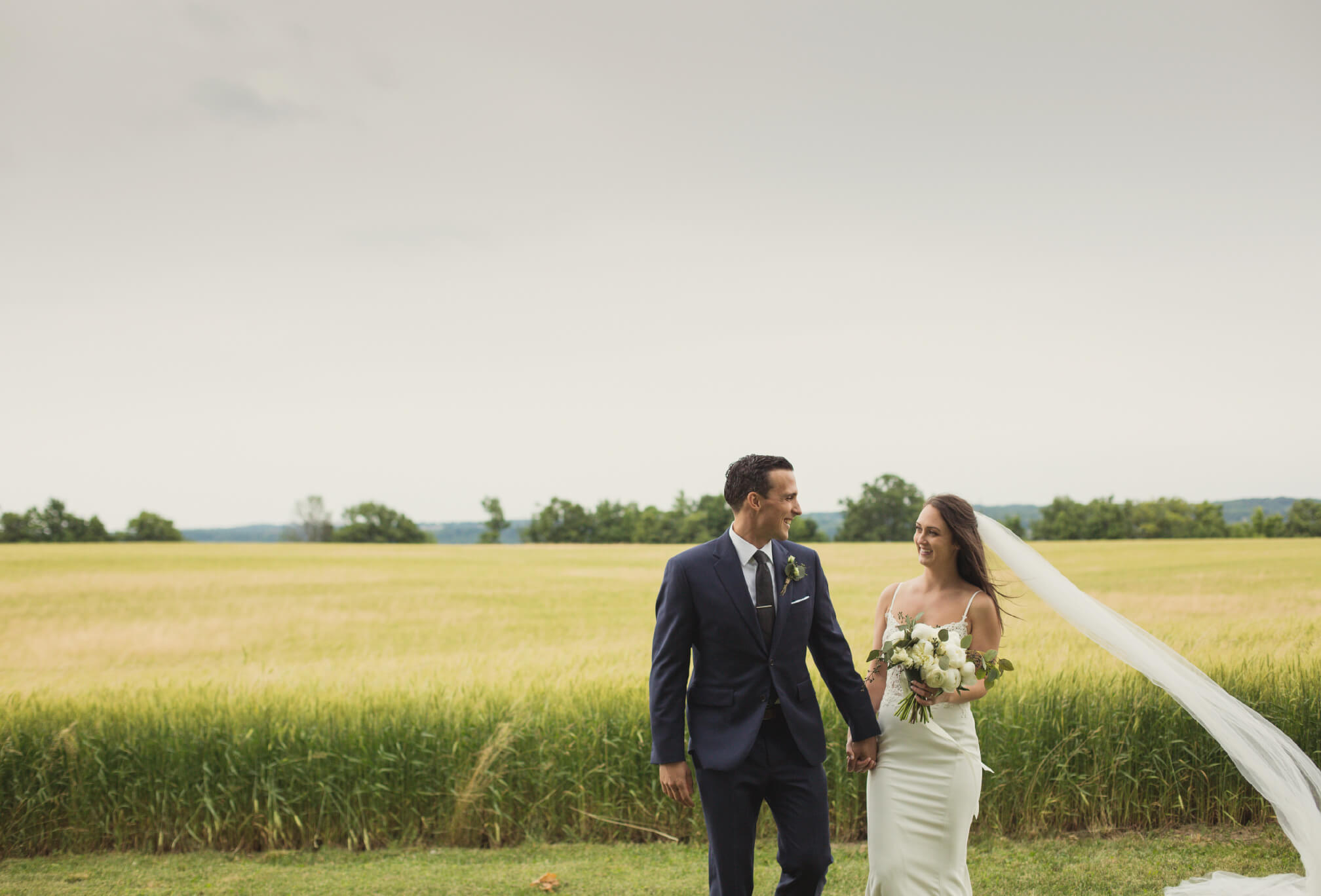 bride and groom walking on farm wedding