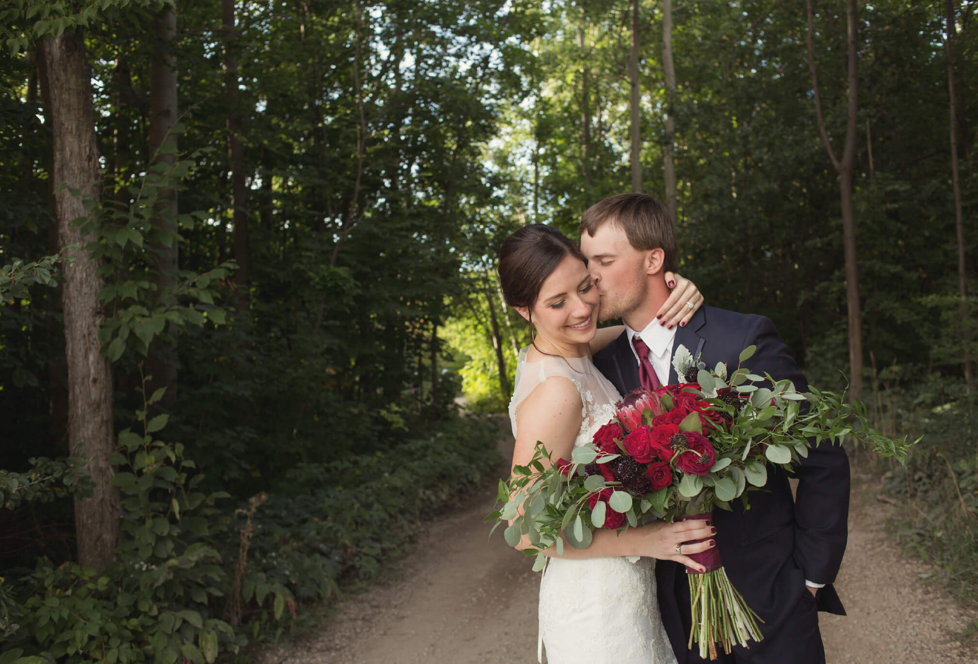 bride and groom kiss on top of blue mountain