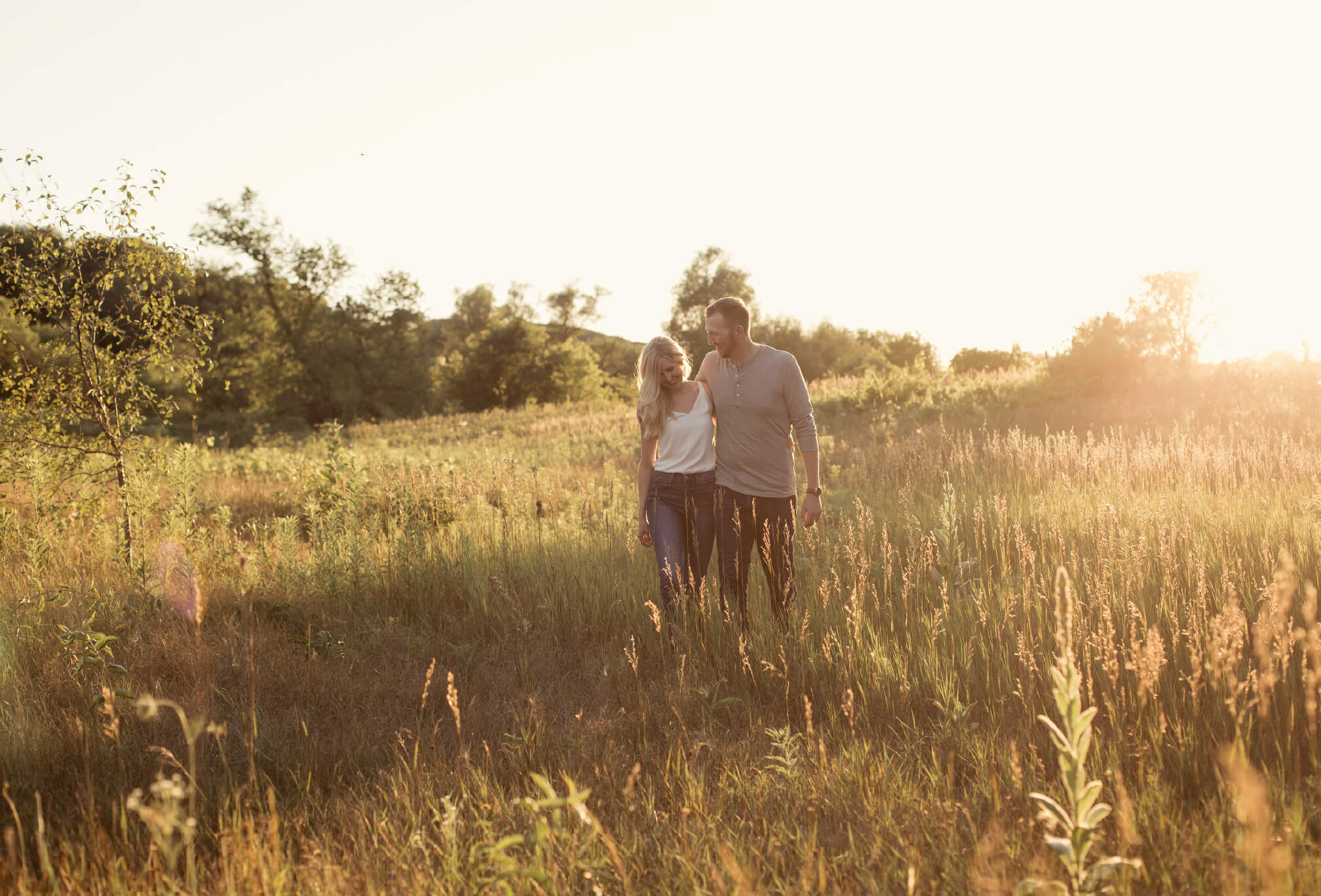 couple walking through field engagement session